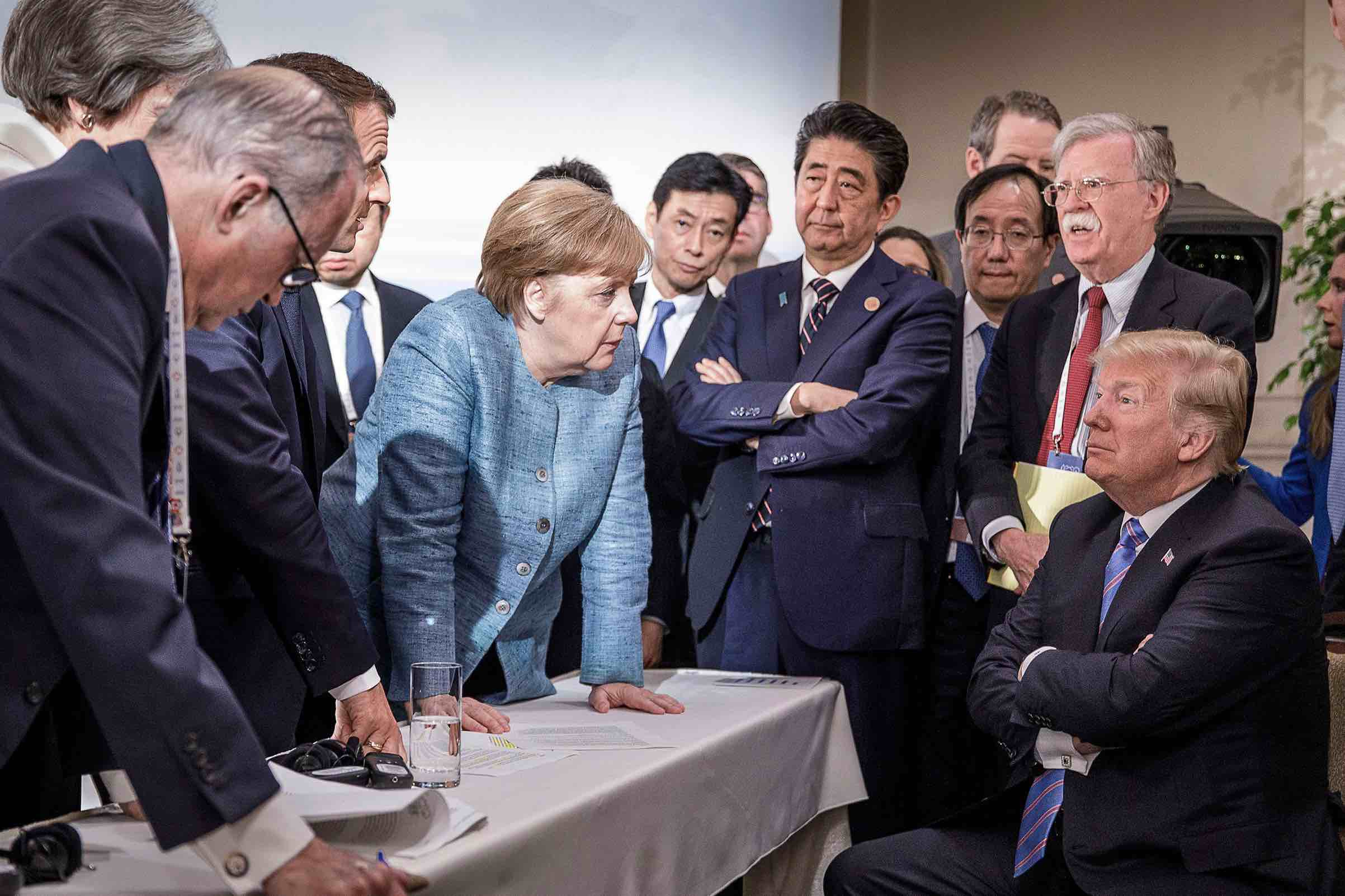 Angela Merkel stands and looks daggers at Trump, while Shinzo Abe is disdainful, with arms crossed, and Donald Trump is petulant, also with arms crossed