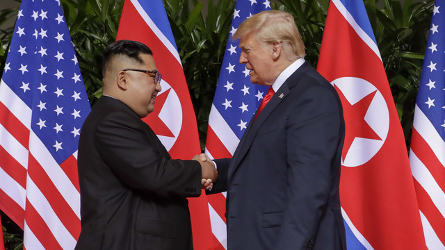 Trump and Kim shake hands at their first summit