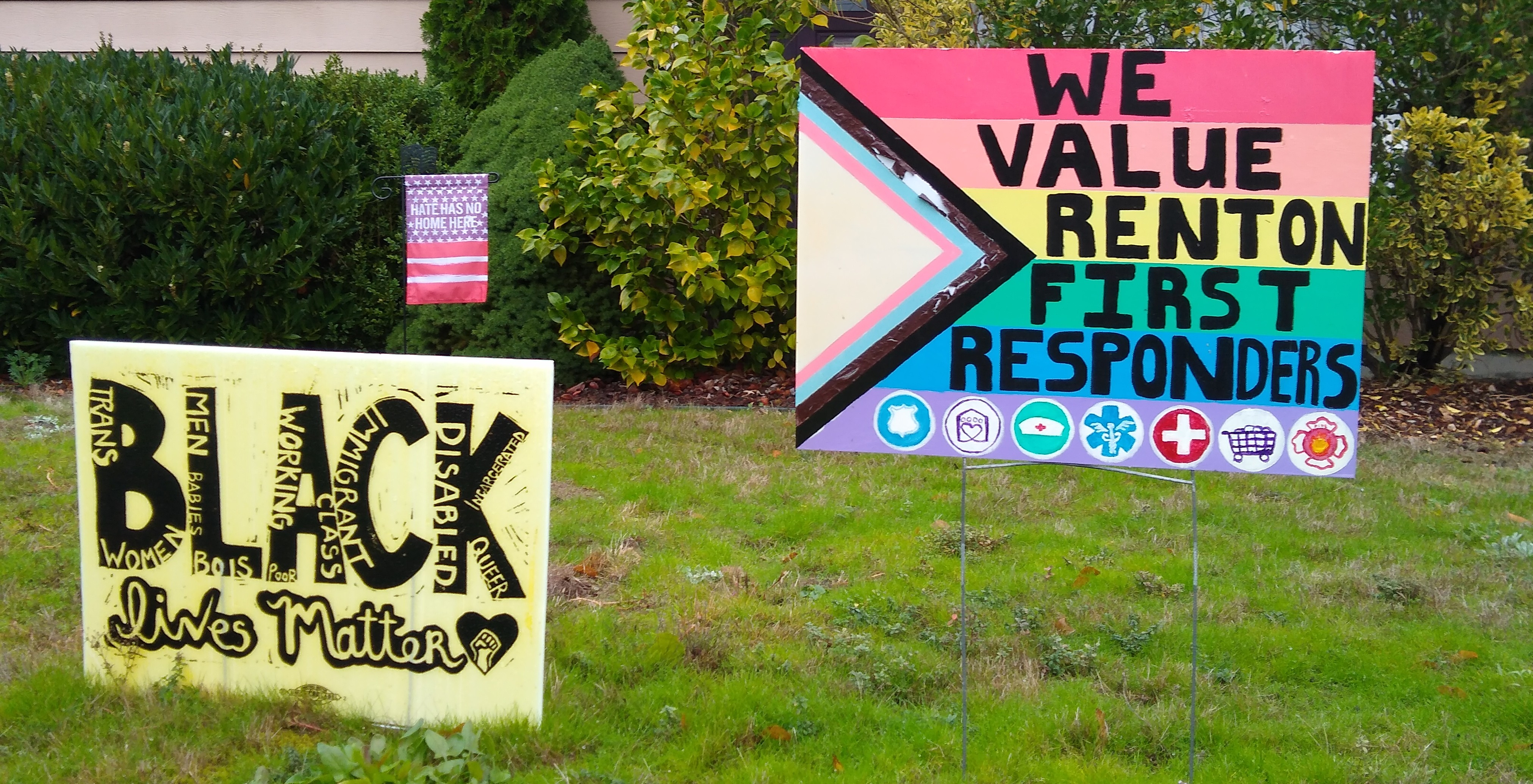 One sign supports Black Lives Matter, the other is rainbow-colored and thanks first responders