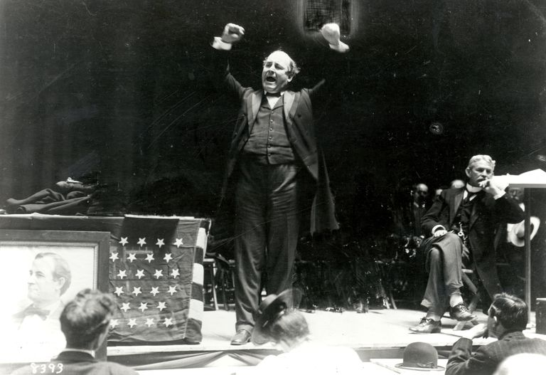 William Jennings Bryan speaks to a crowd, his arms raised above his head for emphasis