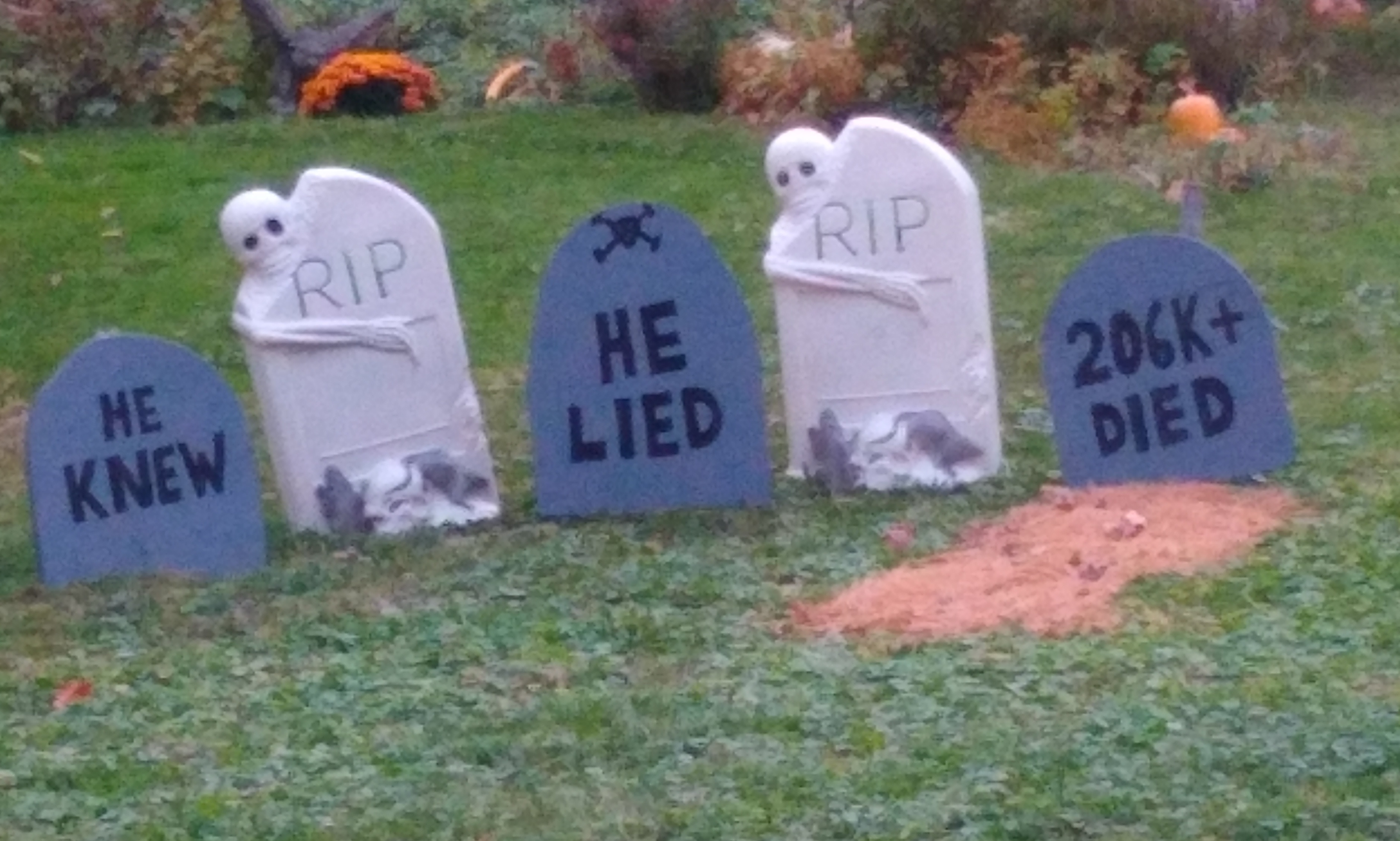 Halloween-style headstone decorations say 'he knew,' 'he lied,' and '206K died'