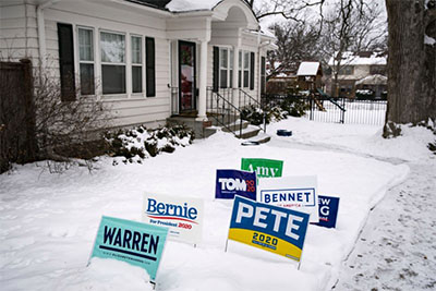House where caucus will take place with yard signs in front