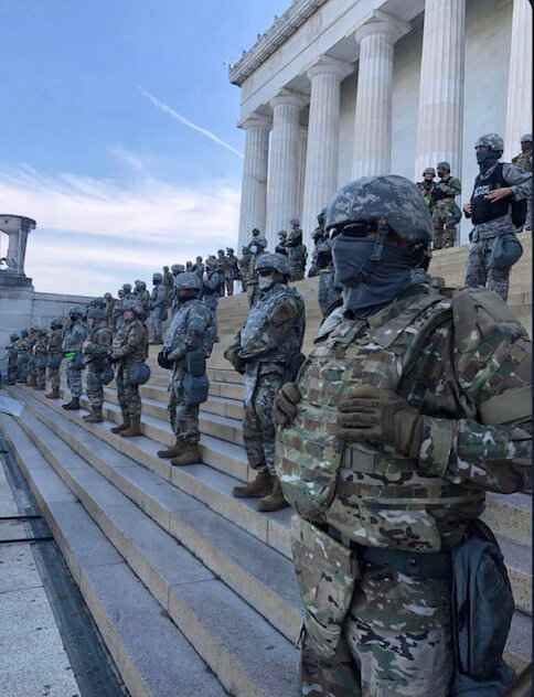 At least 70 men in camouflage and black masks guard the Lincoln Memorial