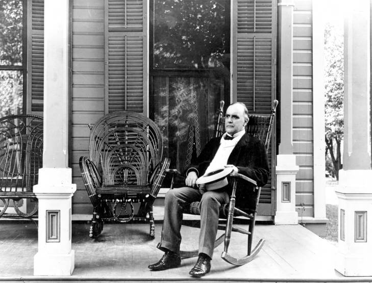 William McKinley, in his suit on his front porch, sitting in a rocking chair and holding a straw hat
