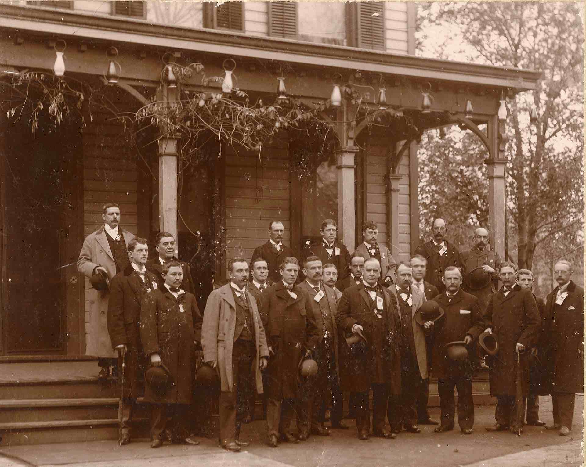 William McKinley, in front of his house, surrounded by about 20 middle-aged white guys in suits