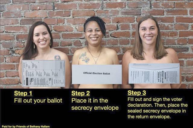 Three topless women have signs in front of their breasts that remind people how to fill out their ballots properly