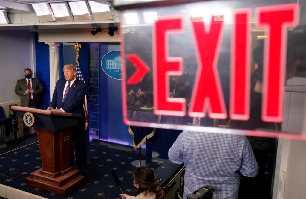 The photo is framed such that an exit sign in the White House appears to be instructing Trump to leave