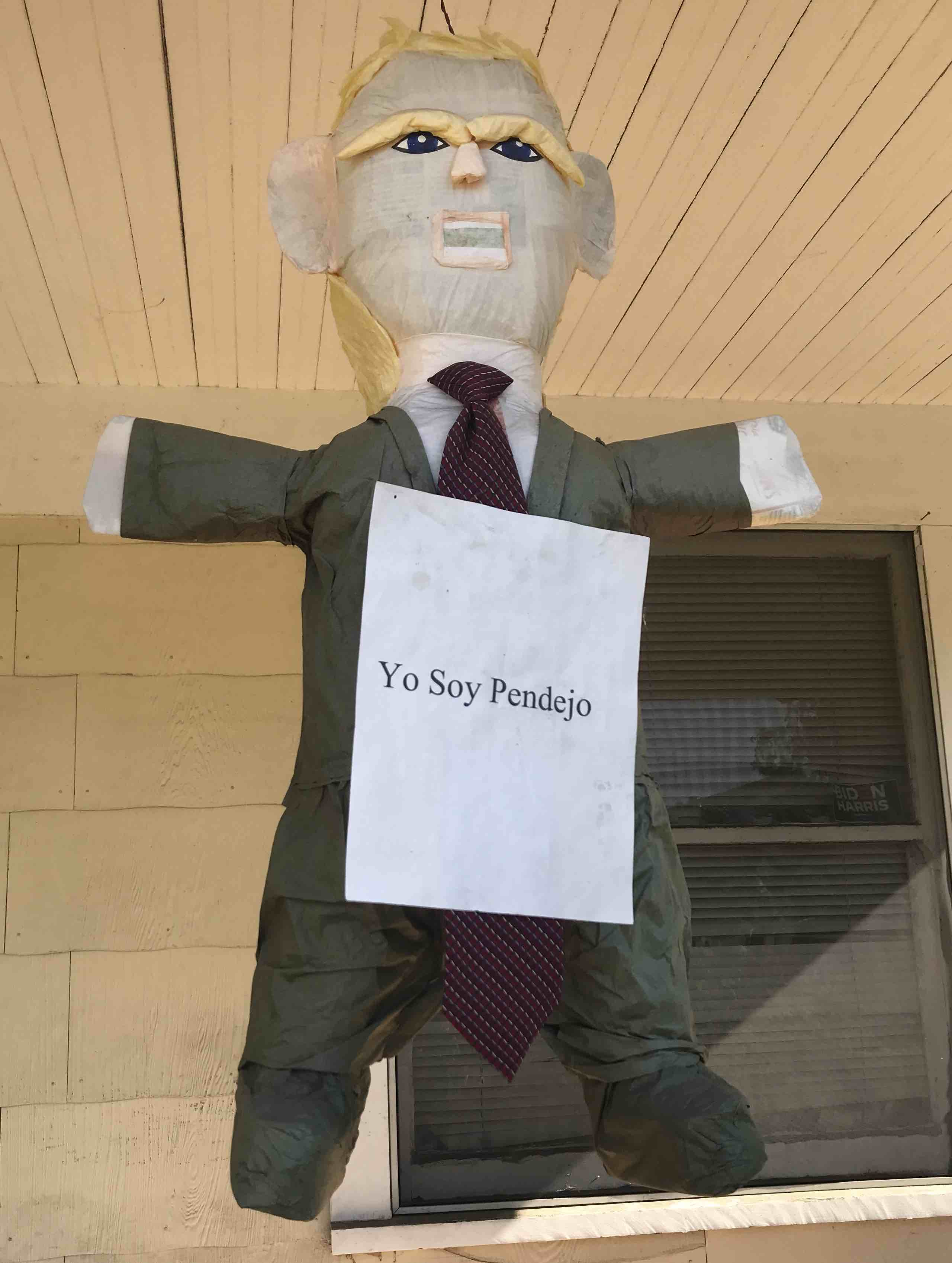 A Trump pinata with a 'Yo soy pendejo' sign attached