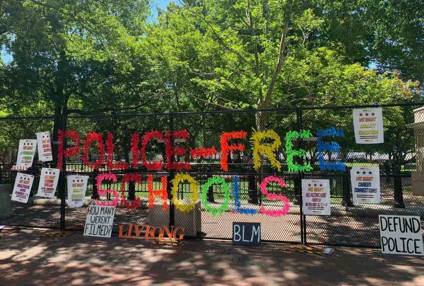 The phrase 'police-free schools' is spelled out in large colorful letters made out of hundreds of tied ribbons, and then surrounded by anti-police placards