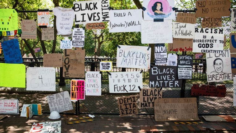 The fence is absolutely blanketed in handmade posters about George Floyd and Black Lives Matter