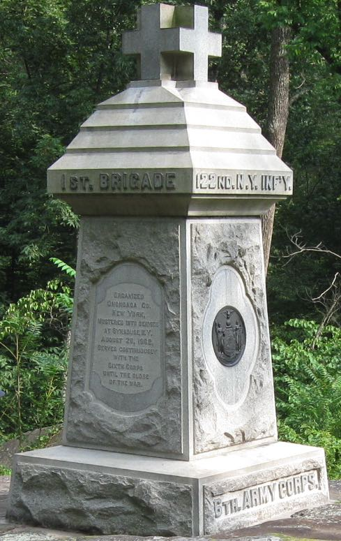 It is about 10 feet tall, with a red cross-type cross on top (though it's not red in color); it's carved out of granite that has grown a little gray over time, and has a bronze medallion  about the size of a small pizza on one side