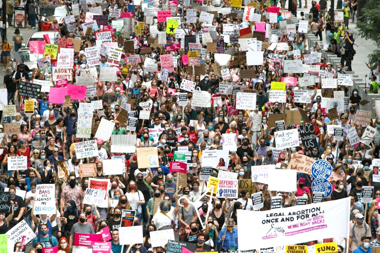 Pro-choice march in Chicago; the crowd is very large,  at least 300 people are visible and they are spillling out of al four sides of the frame