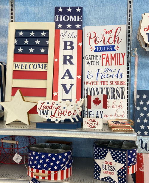 Among a display of wooden, patriotic wall-hangings with flags and patriotic sayings, there is also a small Canadian flag for sale.