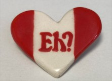 A heart-shaped cloisonne pin with 'eh' on it