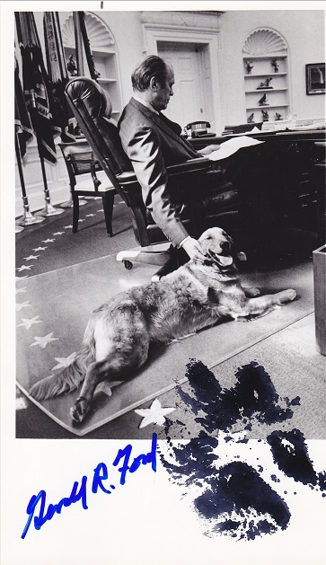 A photo of Gerald Ford in the Oval Office, Liberty the dog on the floor with a paw print in black and Ford's signature in blue
