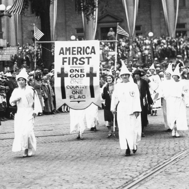 A bunch of Klansmen march down the street circa  1922, carrying a banner that reads 'America First, One God, One Country, One Flag'