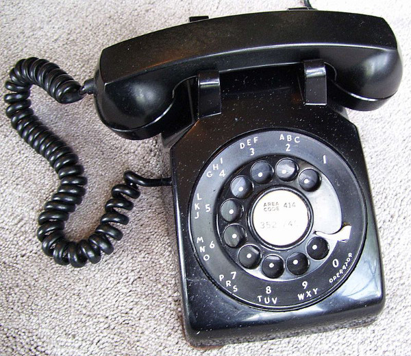 A black phone with  standard handset and rotary dial