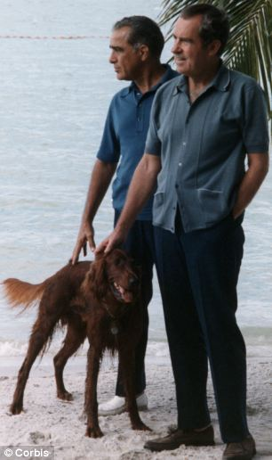 Nixon and Rebozo are dressed in slacks, casual shirts, and are walking a dog along the beach.
