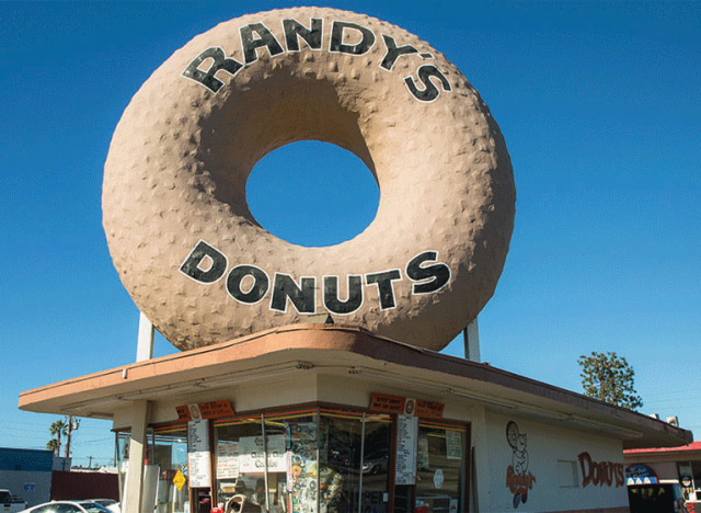 A one-story, plain, basically square-shaped, fairly small donut shop, but with a giant donut on top--at least 50 feet tall--that says 'Randy's Donuts.'