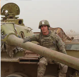 The candidate in full camouflage, with helmet, sitting on a tank