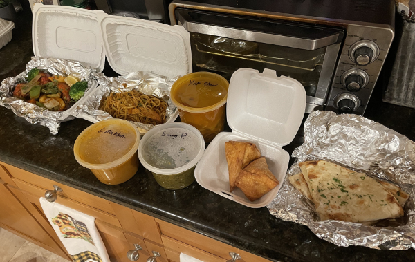 A large amount of take-out food from Tara's, including naan, vegetables, a couple of stews, some noodles, and some sort of turnovers.