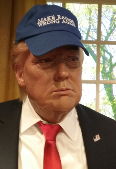 A wax figure that actually  looks like Trump, wearing a blue baseball came that says 'Make Racism Wrong Again'