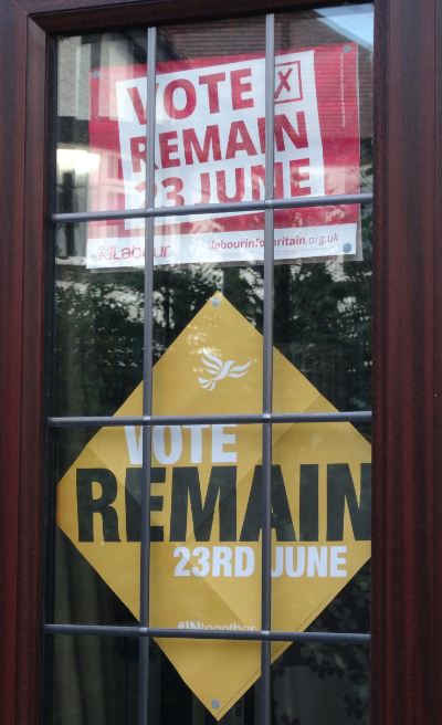 Two signs taped to the window that is inset into a front door; the top one is red and white and has the name of the Labour Party along with 'Vote Remain - 23 June' while the bottom one is yellow, white and black and says 'Vote Remain - 23rd June'