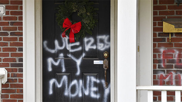 Someone has spray-painted 'Were's my money?' in white spray paint on the front door of McConnell's house